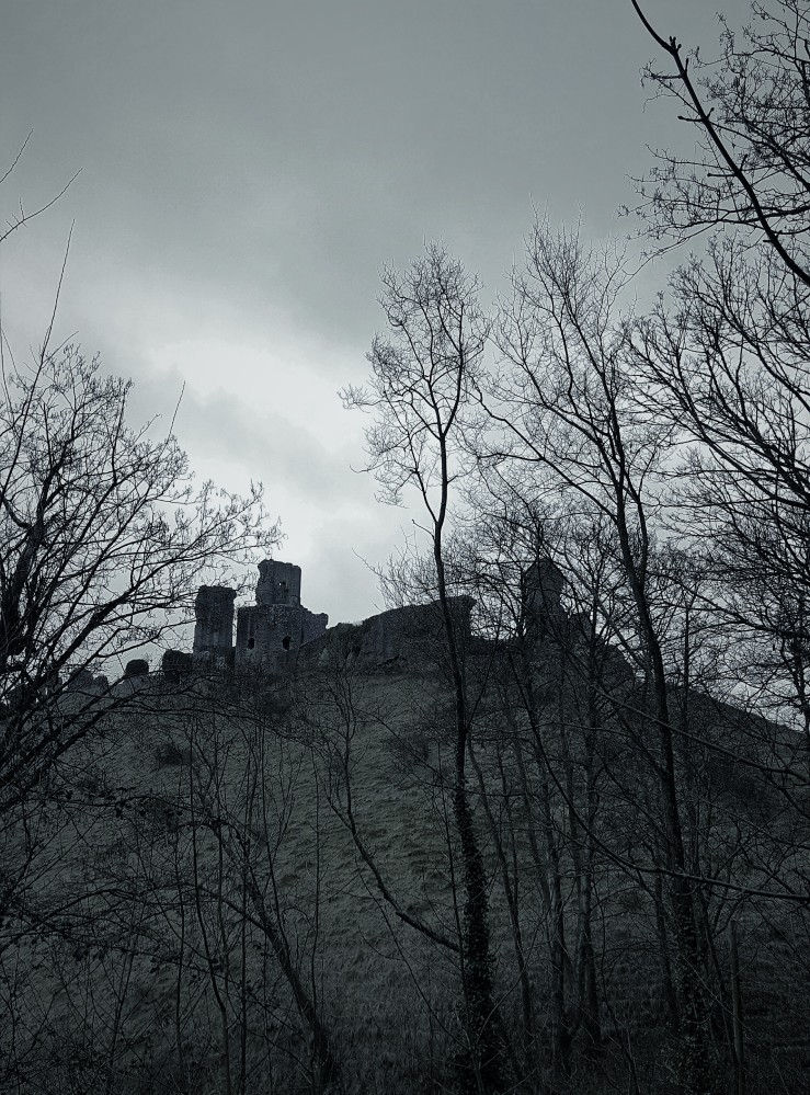 Corfe Castle on a cloudy, rainy day in January. English castle ruins. Gothic style photograph effect.